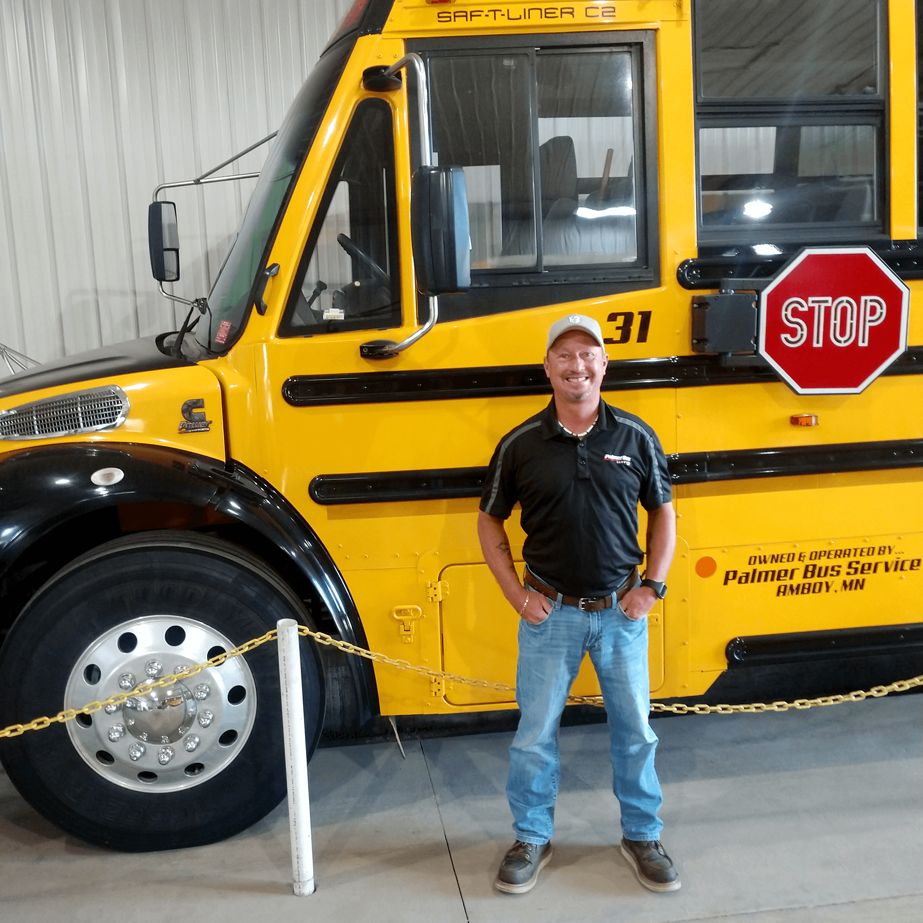 David Goettl, Site Manager for PalmerBus Service of Maple River, standing in front of a school bus.