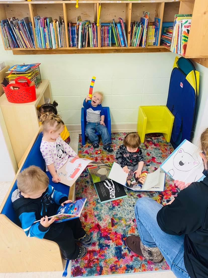 Our little toddler eagle nesters engaging with books at circle time.